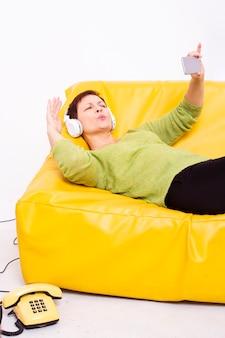 Frau, die auf sofa stillsteht und selfies nimmt