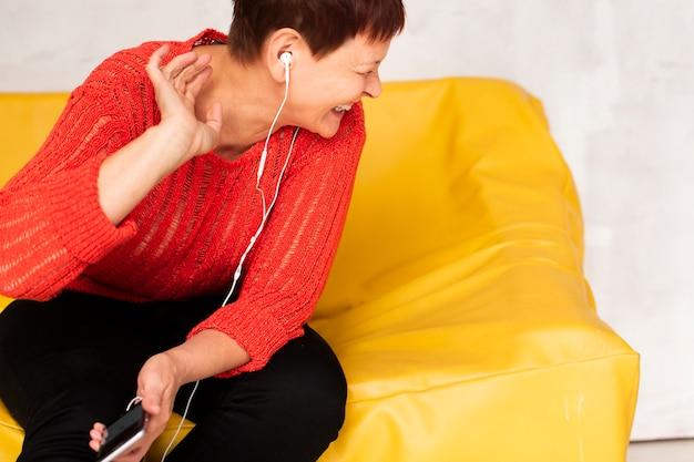 Frau, die auf sofa und hörender musik stationiert
