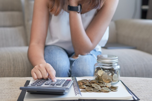Frau, die auf sofa unter verwendung des taschenrechners mit goldmünze und glasflasche sitzt