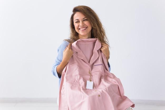 Frau, die auf sofa zu hause sitzt, das online-kleidungskauf öffnet