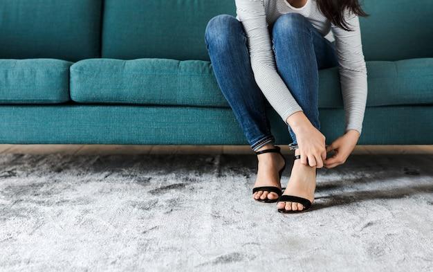 Frau, die auf sofa zu tragenden hohen absätzen sitzt