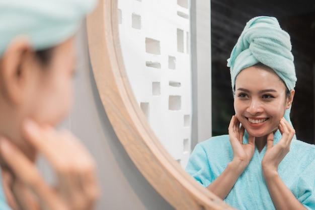 Frau, die auf spiegelung im spiegel nach dusche am badezimmer schaut
