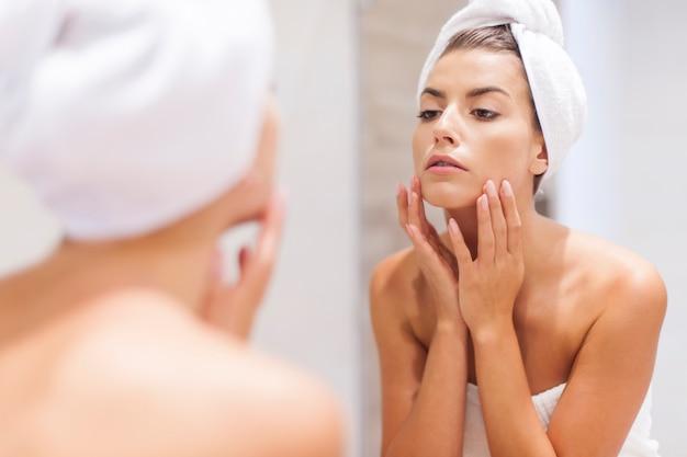 Frau, die auf spiegelung im spiegel nach dusche schaut