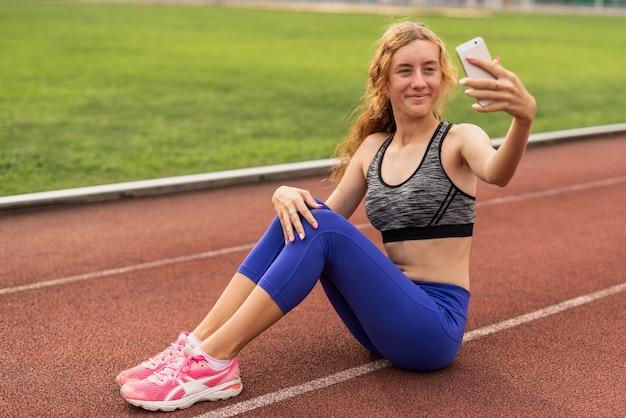Frau, die auf stadion sitzt und selfie nimmt