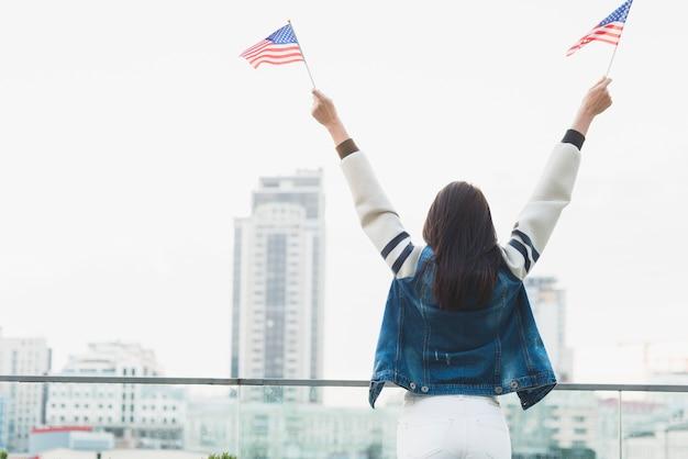 Frau, die auf stadt schaut und amerikanische flaggen wellenartig bewegt