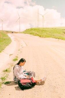 Frau, die auf staubiger straße sitzt und an laptop unter rucksäcken arbeitet