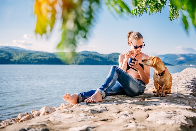 Frau, die auf steinwand mit ihrem hund sich entspannt und plätzchen isst