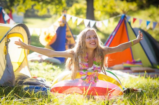 Frau, die auf strandball am campingplatz stützt