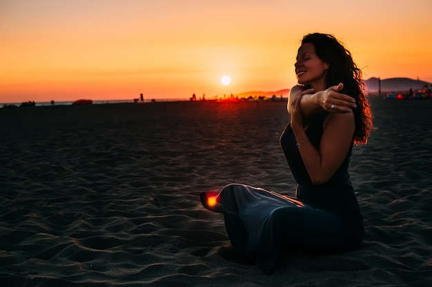 Frau, die auf strandsand sitzt und zur sonnenuntergangzeit sich entspannt