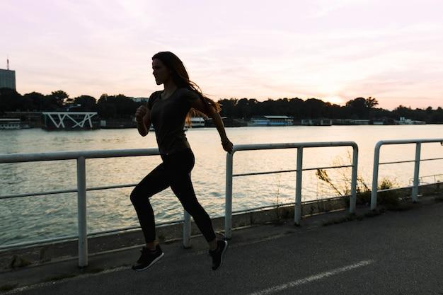 Frau, die auf straße bei sonnenuntergang läuft