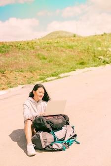 Frau, die auf straße gelegen ist und an dem laptop gesetzt auf rucksäcke arbeitet
