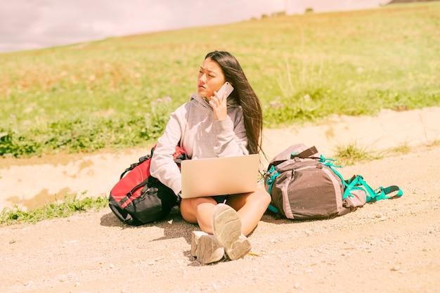 Frau, die auf straße sitzt und am handy unter rucksäcken spricht