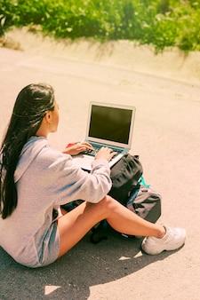 Frau, die auf straße sitzt und an dem notizbuch gesetzt auf rucksäcke arbeitet