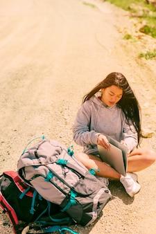 Frau, die auf straße sitzt und an laptop unter rucksäcken arbeitet
