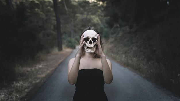 Frau, die auf straße steht und dekorativen menschlichen schädel stattdessen kopf hält