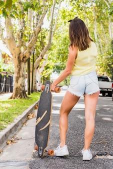 Frau, die auf straße steht und longboard hält