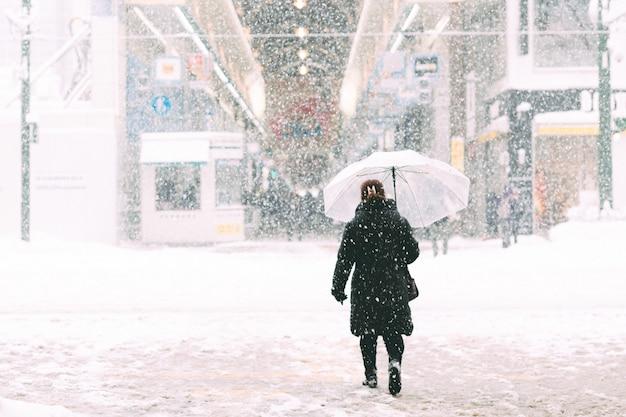 Frau, die auf straßen in der wintersaison geht