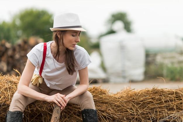 Frau, die auf stroh in einem bauernhof sitzt