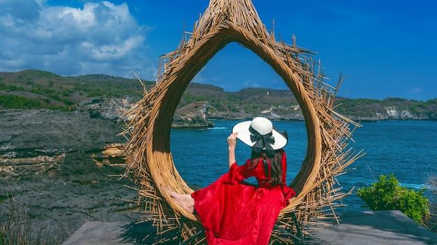 Frau, die auf strohnestern in bali insel, indonesien sitzt.