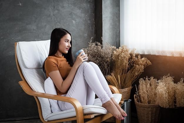 Frau, die auf stuhl, kaffeetasse in den händen halten sitzt und schauen außerhalb des fensters