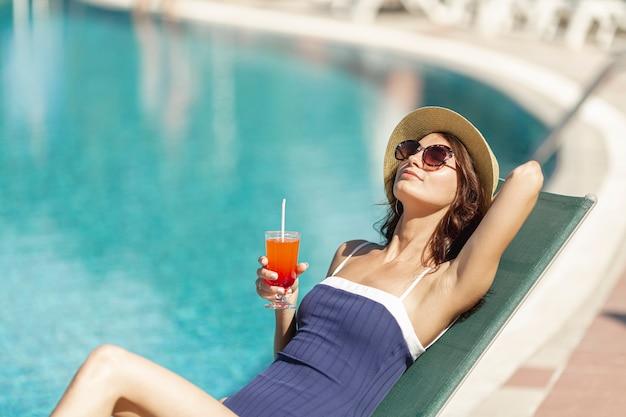 Frau, die auf sunbed holdinggetränk legt