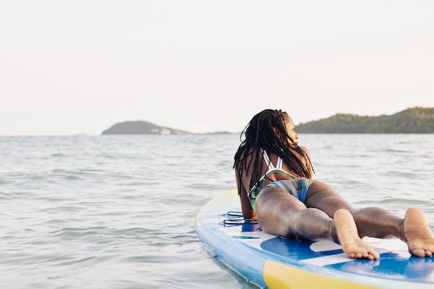 Frau, die auf sup surfbrett liegt