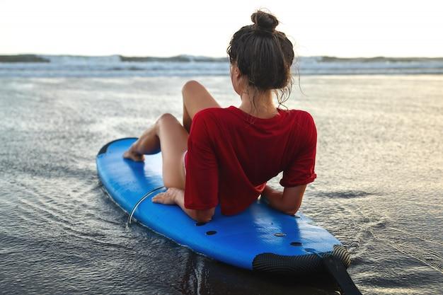 Frau, die auf surfbrett am strand nach ihrer surf-sitzung sitzt