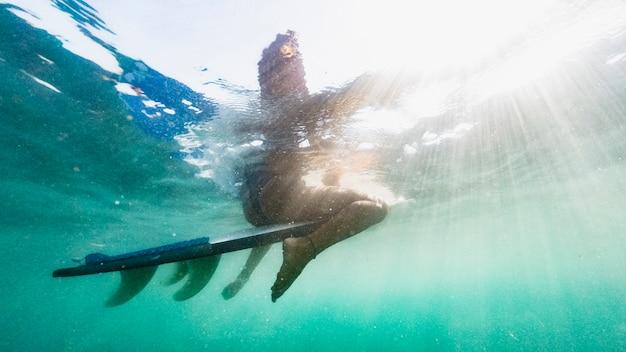 Frau, die auf surfbrett im blauen ozean sitzt