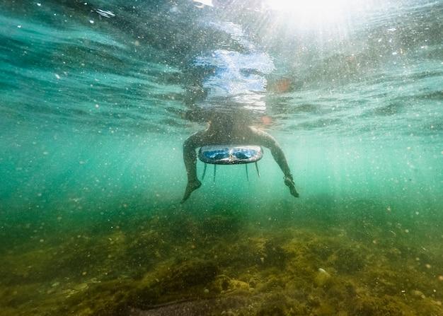 Frau, die auf surfbrett im blauen wasser sitzt