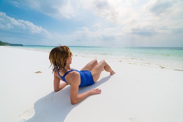 Frau, die auf szenischem weißem sandstrand, hintere ansicht, sonniger tag, transparentes wasser des türkises, wirkliche leute ein sonnenbad nimmt. indonesien, kei-inseln, molukken maluku
