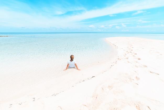 Frau, die auf szenischem weißem sandstrand, hintere ansicht, sonniger tag, transparentes wasser des türkises, wirkliche leute ein sonnenbad nimmt. indonesien, wakatobi inseln