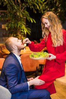 Frau, die auf tabelle sitzt und mann mit salat einzieht