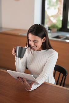 Frau, die auf tablette sitzt und schaut
