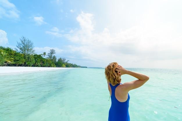 Frau, die auf transparentem wasser des türkises, weißer sandstrand, hintere ansicht, sonniger tag, wirkliche leute ein sonnenbad nimmt