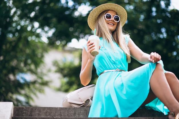 Frau, die auf treppe sitzt und kaffee zum mitnehmen trinkt