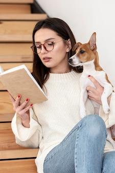 Frau, die auf treppen liest, während sie ihren hund hält