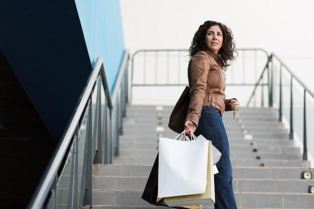 Frau, die auf treppen mit taschen geht