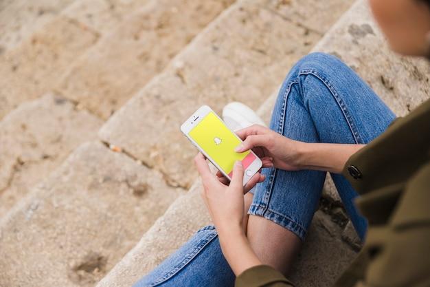 Frau, die auf treppenhaus unter verwendung snapchat app auf smartphone sitzt