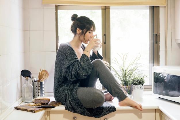 Frau, die auf trinkendem kaffee der küche countertop sitzt