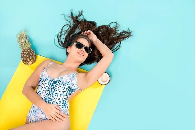 Frau, die auf tuch mit frucht ein sonnenbad nimmt
