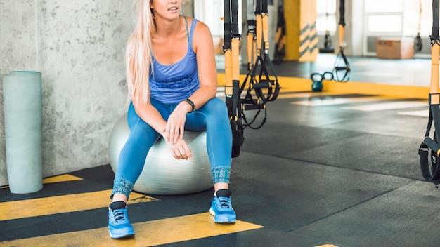 Frau, die auf übungsmatte im fitness-club sitzt