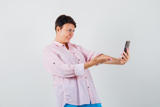 Frau, die auf video-chat im rosa hemd spricht und verwirrt schaut, vorderansicht.