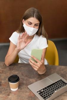 Frau, die auf videoanruf mit maske spricht