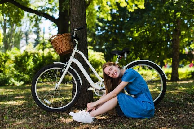 Frau, die auf waldboden nahe bei fahrrad sitzt