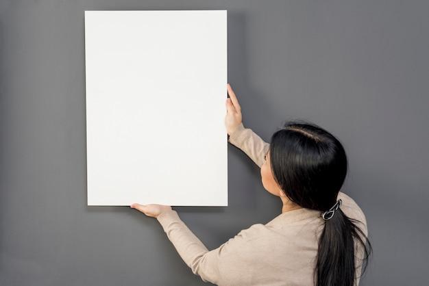 Frau, die auf wand balnk papierblatt sich setzt