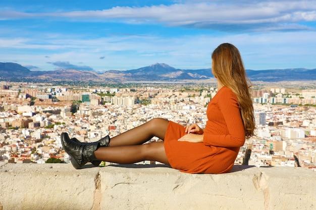 Frau, die auf wand von alicante in spanien sitzt