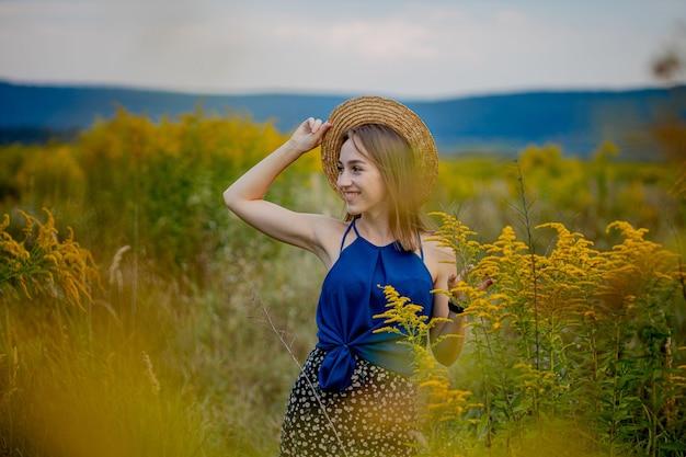 Frau, die auf wildblumen-feld bleibt, das weg copyspace schaut. lächelnd attraktive junge mädchen brünette trägt stilvolle kleidung und hut aufenthalt auf landwirtschaftlichen blumen valley. nette dame auf dem land.