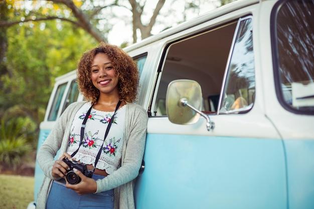 Frau, die auf wohnmobil mit kamera stützt