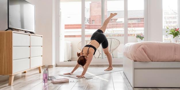Frau, die auf yogamatte ausübt