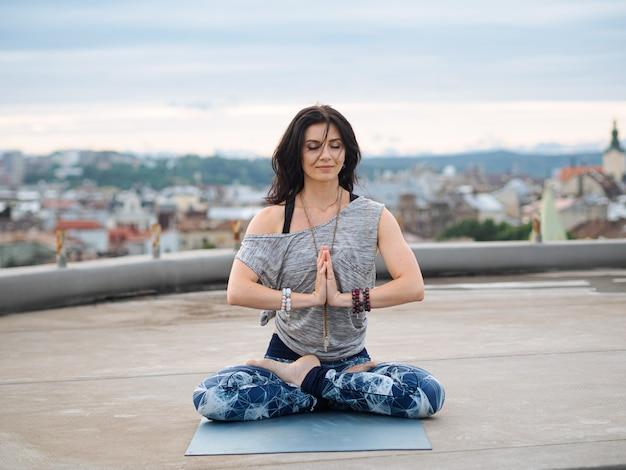 Frau, die auf yogamatte mit geschlossenen augen beim meditieren sitzt